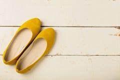 Le ` s de femmes jaunes chausse des ballerines sur le fond en bois Photos libres de droits