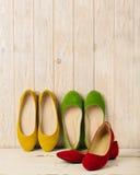 Le ` s de femmes rouge, vert et jaune chausse des ballerines sur le backg en bois Photographie stock