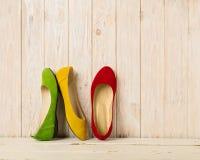 Le ` s de femmes rouge, vert et jaune chausse des ballerines sur le backg en bois Photos libres de droits
