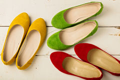 Le ` s de femmes rouge, vert et jaune chausse des ballerines sur le backg en bois Photo stock