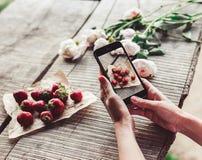 Le ` s de fille remet prendre la photo du petit déjeuner avec des fraises par le smartphone Petit déjeuner sain, Images stock
