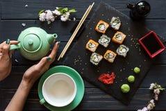 Le ` s de fille remet tenir le thé près des sushi images libres de droits