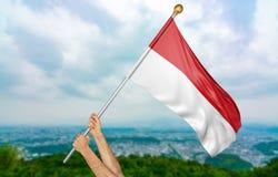 Le ` s de jeune homme remet onduler fièrement l'Indonésie drapeau national dans le ciel, rendu de la partie 3D Images stock