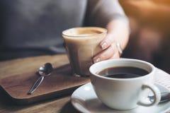 Le ` s de tasse et de femme de café d'Americano remettent tenir la tasse de café de latte sur la table en bois de vintage en café Photo stock