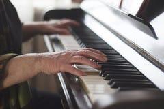 Le ` s de vieille dame remet jouer la musique classique sur le piano à la maison photographie stock libre de droits