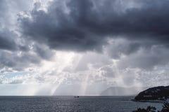 Le ` s du soleil rayonne au-dessus de la mer dans le ciel nuageux images stock