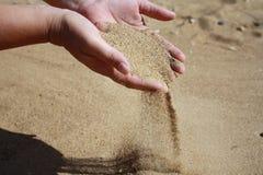 Le sable circule vers le bas des paumes Photographie stock