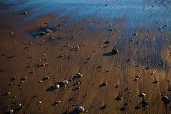 Le sable d'or, consacré par le coucher de soleil, par la mer, a mouillé de la vague de reflux images stock