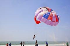 Le sable vole pendant que le parapentiste décolle Photo stock
