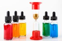 Le sablier a commencé le compte à rebours et les bouteilles en verre transparentes remplies ont coloré le liquide avec le compte- Photographie stock