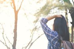 Le sac à dos asiatique heureux de fille à l'arrière-plan de parc et de forêt, détendent t Images stock