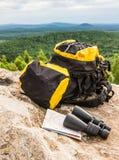 Le sac à dos jaune avec les jumelles de touristes d'équipement tracent la vue de tourisme de voyage photos libres de droits