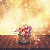 le sac à Noël 3D de cadeaux sur la table en bois contre l'or tient le premier rôle le Ba Image stock