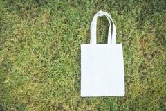 Le sac blanc ? achats de tissu de sac d'eco de tissu de toile d'emballage sur le fond d'herbe verte/z?ro d?chets emploient moins  photographie stock libre de droits