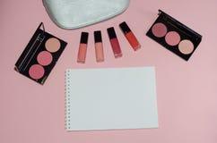 Le sac cosmétique de femme, composent des produits de beauté sur le fond rose, carnet Rouge à lèvres rouge et rose Brosses de maq Photos libres de droits