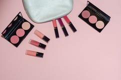 Le sac cosmétique de femme, composent des produits de beauté sur le fond rose Rouges à lèvres et palettes roses de fard à joues P Photo libre de droits