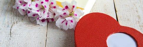 Le sac de papier avec les fleurs fraîches et le coeur enferment dans une boîte le cadeau sur la table en bois images stock