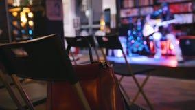 Le sac est sur la chaise - pièce vide devant le guitariste au concert - guitare acoustique, microphone, club banque de vidéos