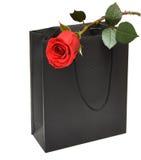 Le sac noir de cadeau avec le rouge s'est levé Image libre de droits
