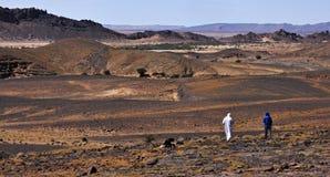 Le Sahara chaud et sec rocheux et montagneux au Maroc avec deux personnes sortantes photographie stock libre de droits
