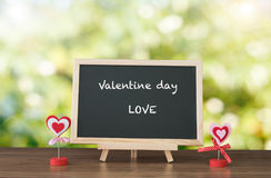 Le Saint Valentin et l'AMOUR textotent sur les WI noirs de dessus de table de conseil et en bois Image stock