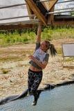 Le salite della ragazza sulle barre sopra acqua Corsa di eroi Fotografia Stock