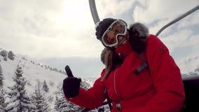 Le salite dello sciatore della donna sulla seggiovia alla cima della montagna mostra il pollice su stock footage