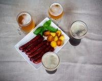 Le salsicce di maiale sul piatto bianco, vetri della birra, hanno arrostito le patate Fotografia Stock