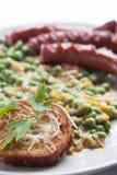 Le salsiccie con i piselli guarniscono e prezzemolo immagine stock