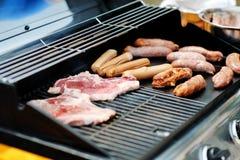 Le salsiccie e le bistecche che cucinano su un barbecue grigliano Fotografie Stock Libere da Diritti