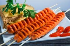 Le salsiccie fatte su una griglia e su un piatto di verdi Fotografie Stock