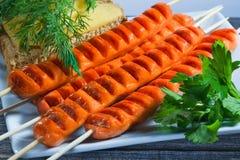 Le salsiccie fatte su una griglia e su un piatto rettangolare di verdi Fotografia Stock