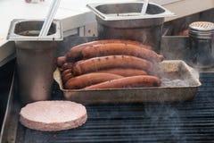 Le salsiccie fritte su una griglia sulla via grigliano Immagine Stock