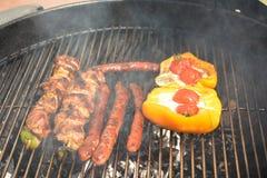 Le salsiccie, la carne ed il pepe sul barbecue grigliano Fotografie Stock Libere da Diritti