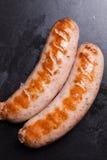 Le salsiccie su una griglia nera del fondo fritta taglia Fotografia Stock