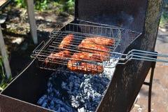 Le salsiccie una griglia sono fritte su un addetto alla brasatura Fotografia Stock