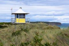 Le salvavite di una spuma si elevano sulle dune di una spiaggia australiana della spuma Fotografia Stock