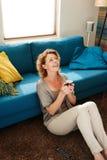 Le sammanträde för äldre kvinna på golv med varmt kaffe royaltyfria foton