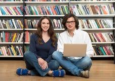 Le sammanträde för ung flicka och för ung man på golvet i liben Arkivbild