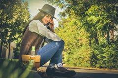 Le sammanträde för ung kvinna på gatan som talar på den smarta telefonen fotografering för bildbyråer