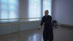Le samouraï dans le kimono mène le combat d'ombre à l'aide de l'épée de catana clips vidéos