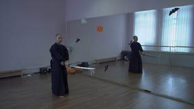 Le samouraï dans le kimono mène le combat d'ombre à l'aide de l'épée de katana dans le hall avec des miroirs dans le thème de banque de vidéos