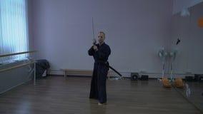 Le samouraï exécute le kendo de kata avec l'épée du ` s de katana dans la salle de gymnastique banque de vidéos