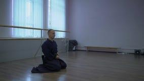 Le samouraï s'assied sur le plancher et attache l'épée de katana à la ceinture de kimono, puis aux hausses clips vidéos