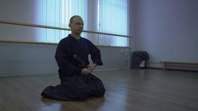 Le samouraï s'assied sur le plancher et lie l'épée du ` s de katana à la ceinture, puis aux hausses banque de vidéos