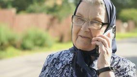 Le samtal för gammal kvinna genom att använda smartphonen utomhus arkivfilmer