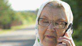 Le samtal för gammal kvinna genom att använda smartphonen utomhus stock video