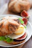 Le sandwich avec l'oeuf poché, le fromage et les figues fraîches se ferment  photo libre de droits