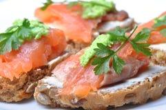 Le sandwich avec les saumons fumés a isolé Photographie stock