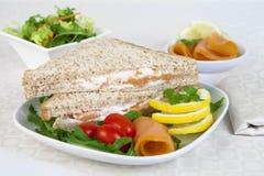 Le sandwich avec les saumons fumés a servi sur un plat blanc comme un apeti photographie stock libre de droits